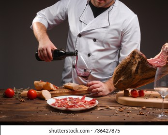 The cook pours the wine into a glass. A bottle of wine, spices, jamon, tomatoes, a wooden table. Closeup image