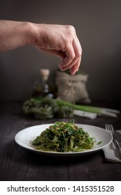 the cook prepares green pasta with nuts and green onions