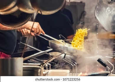 The cook prepares pasta in a restaurant