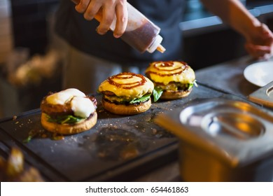 Cook preparing burger adding the sauce on the cream cheese. Three burgers.