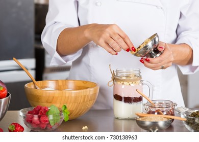 Cook preparing a dessert based on yogurt and cereals