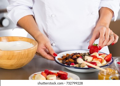 Cook preparing a dessert made with yogurt fruits and cereals