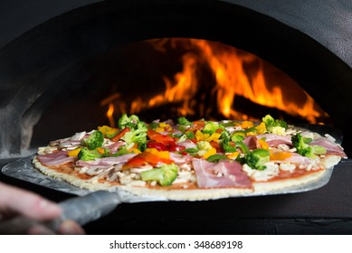 The cook puts pizza bread into wood-burning stove.
