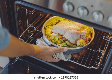 Cook putting raw chicken with vegetables to the oven. Home cooking concept.