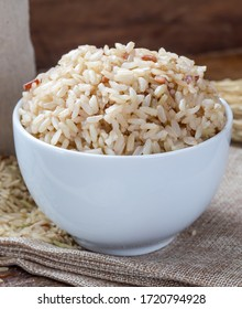 Cook and raw brown rice in white ceramic bowl on wood table and wood background with spoon. Copy space. Food issue.