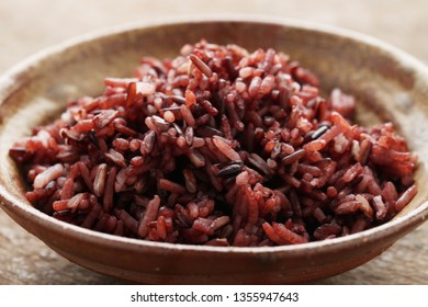 Cook riceberry rice on wood background.Thai organic rice.