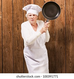 Cook senior woman angry trying to hit with a pan against a wooden wall