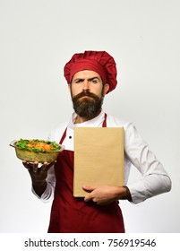 Cook with serious face in burgundy uniform holds baked dish and recipe book. Chef holds bowl with potato casserole and cook book. Man with beard on white background. Catering and eating out concept