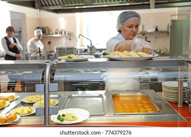 Cook sets pots and dishes on a full lunch service station of a dining room. Day of opened door for mass-media in the Ukrainian parliament canteen. November 23. 2017. Kiev, Ukraine