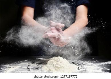 Cook slams splash hands with flour. White dust cloud of flour