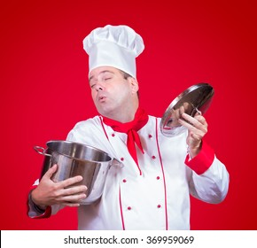 Cook smell the open pot in red background. Dreamy chef holding in hand an open pot. The master chef sniffing the smell of food from the pot.