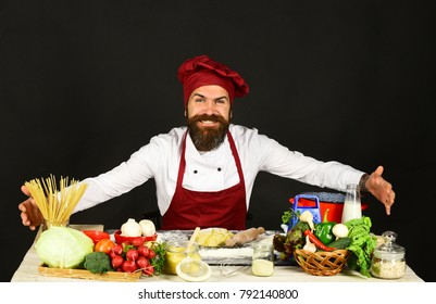 Cook with smile in burgundy uniform near ingredients. Chef pretends to hug pasta, vegetables and dough on table. Cooking process concept. Man with beard sits by countertop on black background.