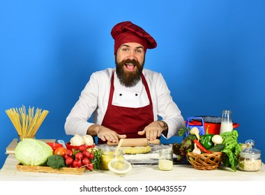 Man beard holds recipe book menu stock photo royalty free cook with smile in burgundy uniform rolls dough with rolling pin man with beard sits forumfinder Image collections