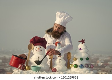 Cook, snowmen and snow xmas tree on blue sky. Hipster with ladle in white uniform. Man in chef hat ladling soup on winter day. Christmas and new year holidays food. Cooking and diet concept.