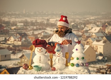 Cook, snowmen and snow xmas tree on blue sky. Cooking and diet concept. Christmas and new year holidays food. Man in santa hat ladling soup on winter day. Hipster with ladle in white uniform.