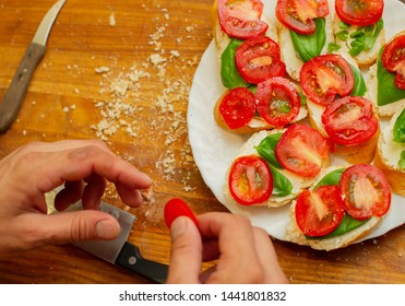 The cook spreads the cottage cheese on the bread with tomato. Men's hands spreading soft cheese on a French loaf. Vegetarian sandwiches on a wooden board. Healthy food. Seasonal food.