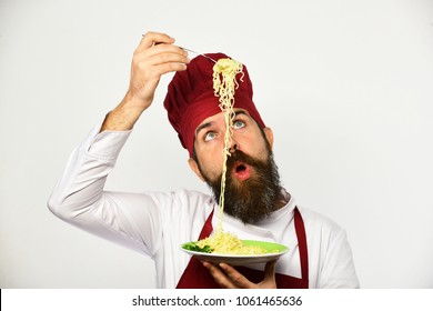 Cook with surprised face in burgundy uniform holds fork and plate. Chef eats italian or asian noodles.