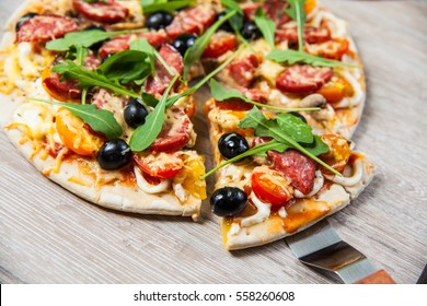 Cook takes a shovel one piece of pizza with cheese olives and salami, mushrooms and tomatoes, arugula. On a wooden stand.
