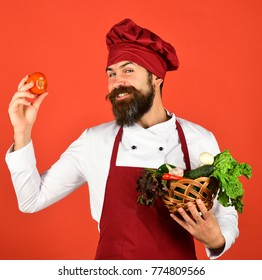 Cook with tricky face in burgundy uniform holds tomato and vegetables in wicker bowl. Healthy cooking concept. Chef holds lettuce, garlic, pepper and mushrooms. Man with beard on red background.
