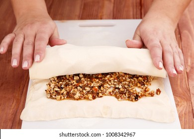 Cook turns the roll from flour dough with walnut filling