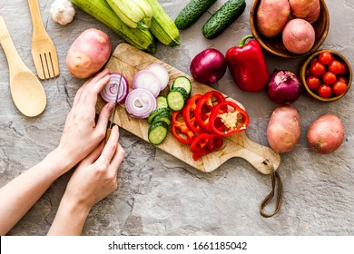 Kochen Sie Gemüse. Pfeffer-Handschnitt bei Herbsternte auf grauem Hintergrund, oben nach unten