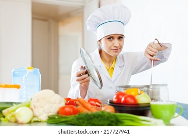Cook in white hat looks into the saucepan in kitchen