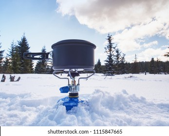 Cook at an winter outdoor campsite. Outdoor cooking in winter with a small black couldron above burning gas cooker