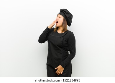 cook woman yawning lazily early in the morning, waking and looking sleepy, tired and bored against white background