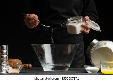 The cook is working making the dough, sprinkled with sugar on a black background. Freezing in motion. Cooking Baking Closeup