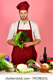 Cook works in kitchen with vegetables and tools. Chef with serious face holds bunches of lettuce and parsley on pink background. Vegetarian meal concept. Man in cook hat and apron with salad.