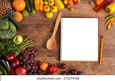 Cookbook. Copy space / studio photography of open blank ring bound notebook surrounded by a fresh vegetables and pencil on old wooden table