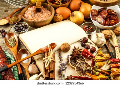 Cookbook and spice on a wooden table. Food preparation. An old book in the kitchen. Recipes for food.