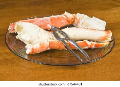 Cooked Alaskan Crab Legs on a Glass Plate and a Nut Cracker