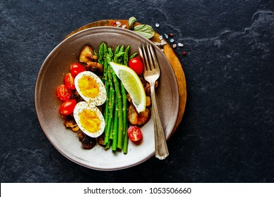 Cooked aspargus, tomatoes, mushrooms and eggs breakfast plate over black stone copy space background. Energy boosting food concept. Top view. Flat lay.