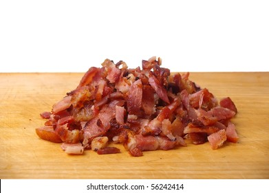 cooked bacon bits on wooden chopping  board