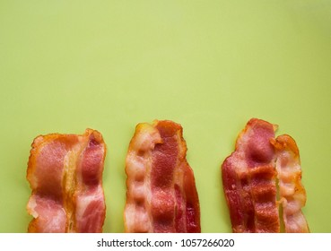Cooked bacon rashers on green plate with copy space