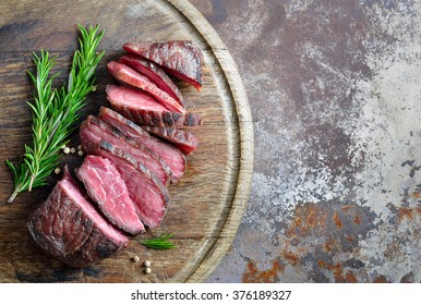 Cooked beefsteak cut on a board, top view