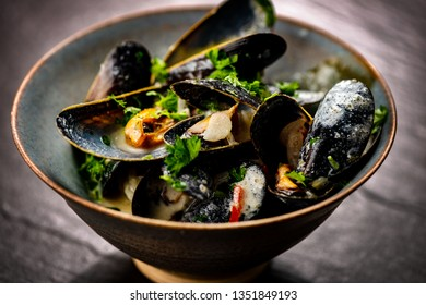 Cooked Blue mussels in clay dish close up
