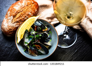 Cooked Blue mussels in clay dish with bread and white wine glass