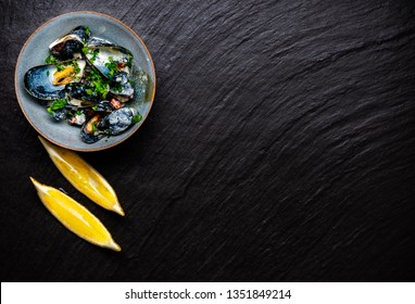 Cooked Blue mussels in clay dish with lemon