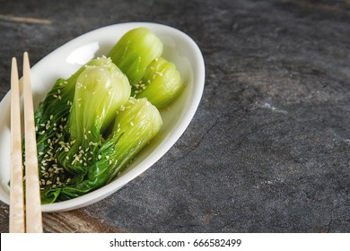 Cooked bok choy or chinese cabbage with sesame and  soy sauce. Simple background. Healthy food. Lifestyle