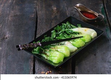 Cooked bok choy with sesame seeds and chili pepper olive oil in black square ceramic plate with black chopsticks over old wooden table. Rustic style