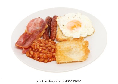 Cooked breakfast, sausage, bacon, fried bread, fried egg and baked beans on a plate isolated against white