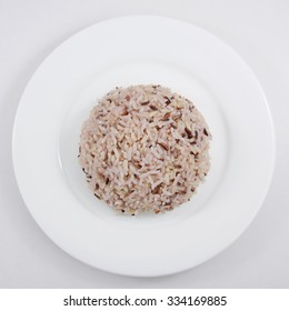 The cooked brown rice on the white plate.
