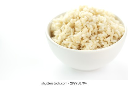 cooked brown rice in white cup on white background.