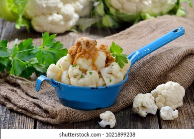 Cooked cauliflower topped with bread crumbs browned in butter and served steaming hot  in an old enamel pot