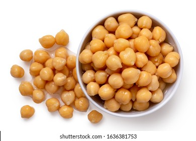 Cooked chick peas in a white ceramic bowl isolated on white. Spilled chick peas. Top view.