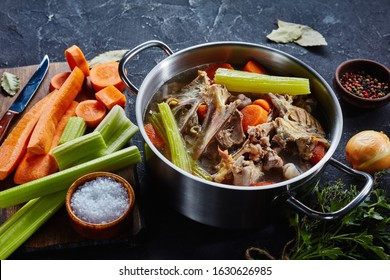 cooked chicken stock with vegetables and aromatic herbs in a stockpot, ingredients on a kitchen worktop, close-up