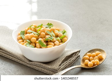 Cooked chickpeas on white bowl, healthy and vegetarian food, close up