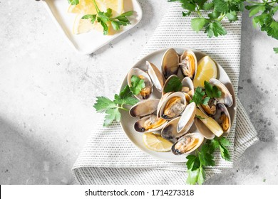 Cooked clams in a ceramic plate on a light gray table. Seafood dish. The view from the top